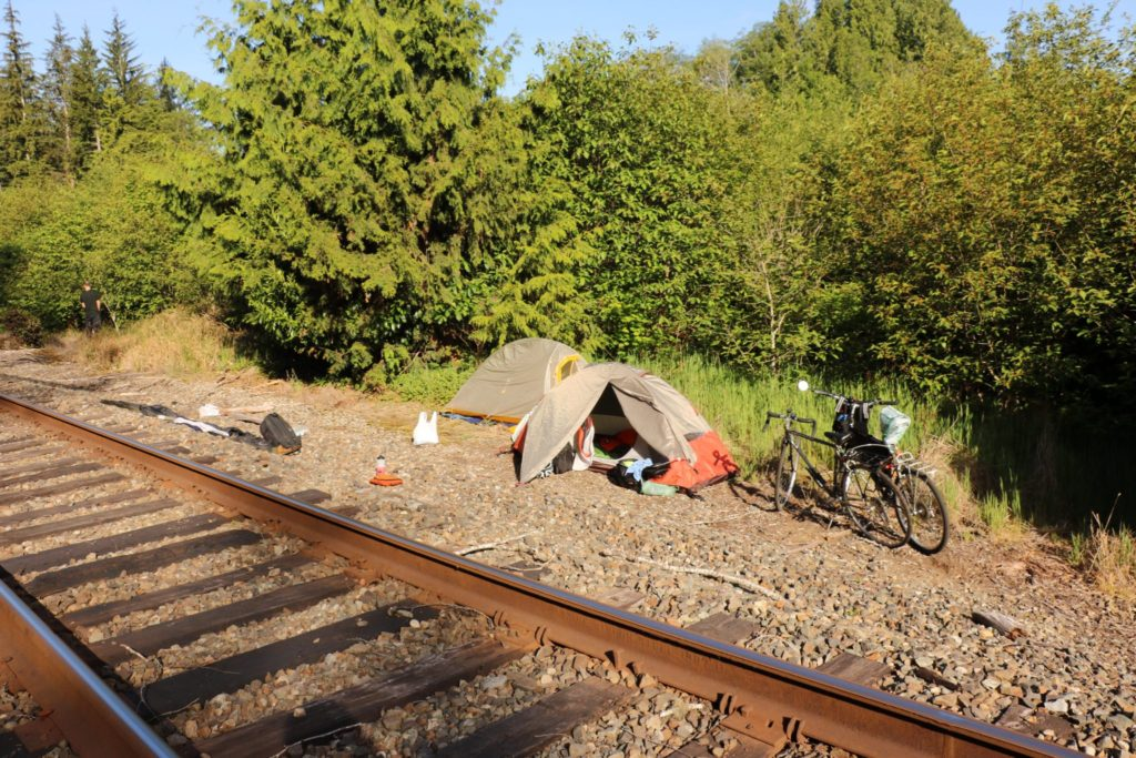 Tents set up by railroad tracks