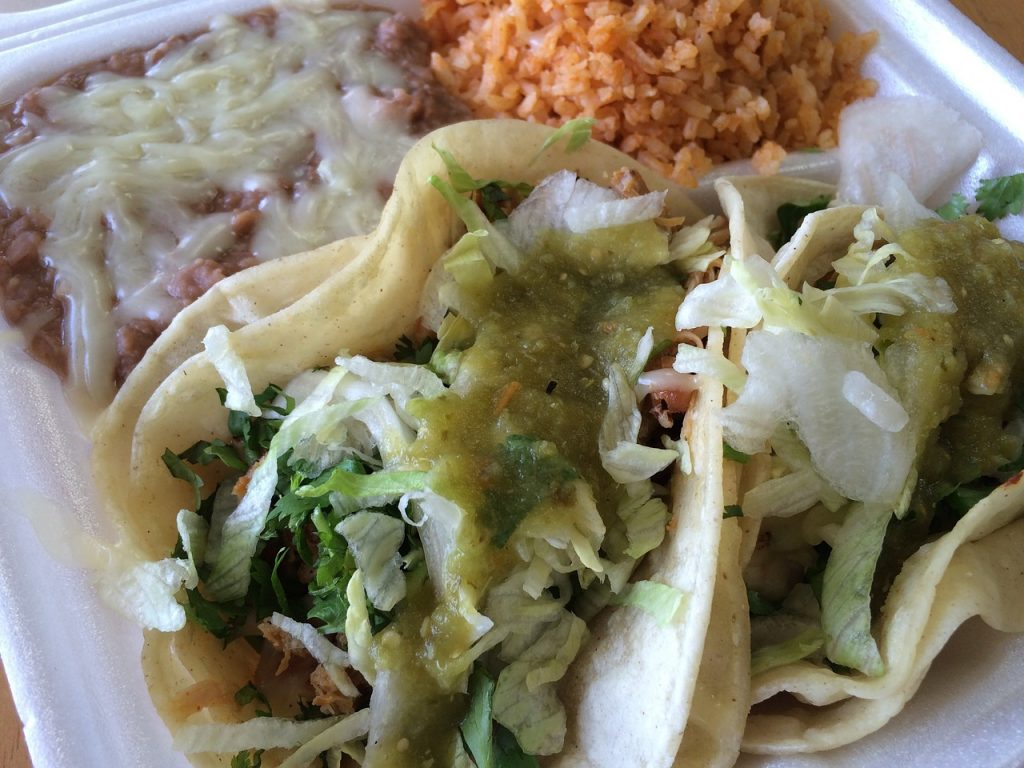 A taco platter with rice and beans