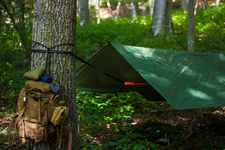 A camping tarp set up over a hammock