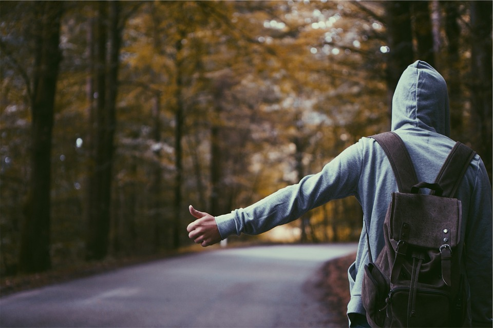 A man hitchhiking on the side of a road
