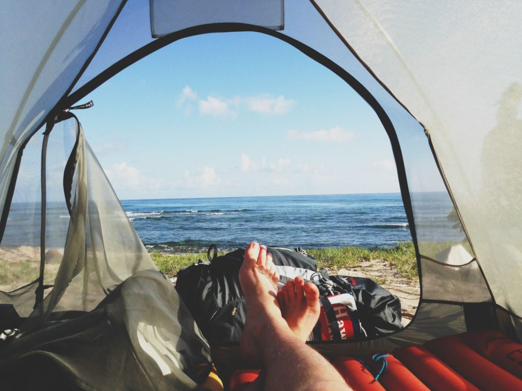 Looking out at the ocean from inside of a double wall tent pitched on the beach.