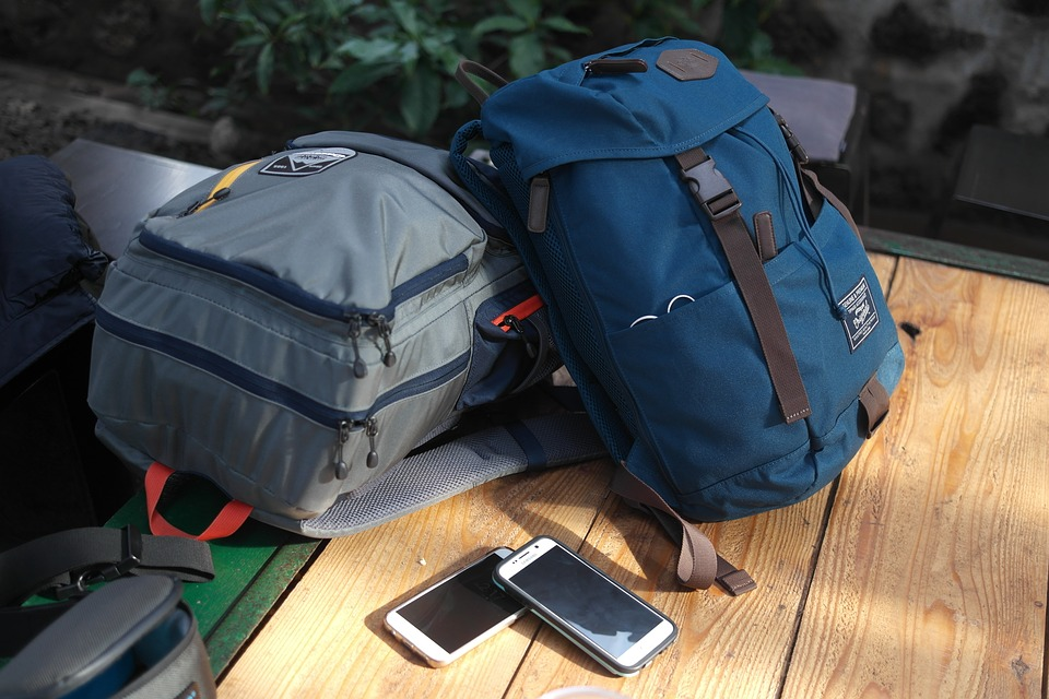 travel backpacks and phones sitting on a table