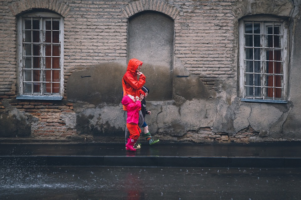 a family walking down a street while wearing rain jackets