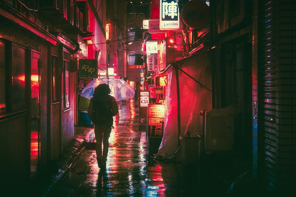 a tourist using an umbrella on a rainy night in the city