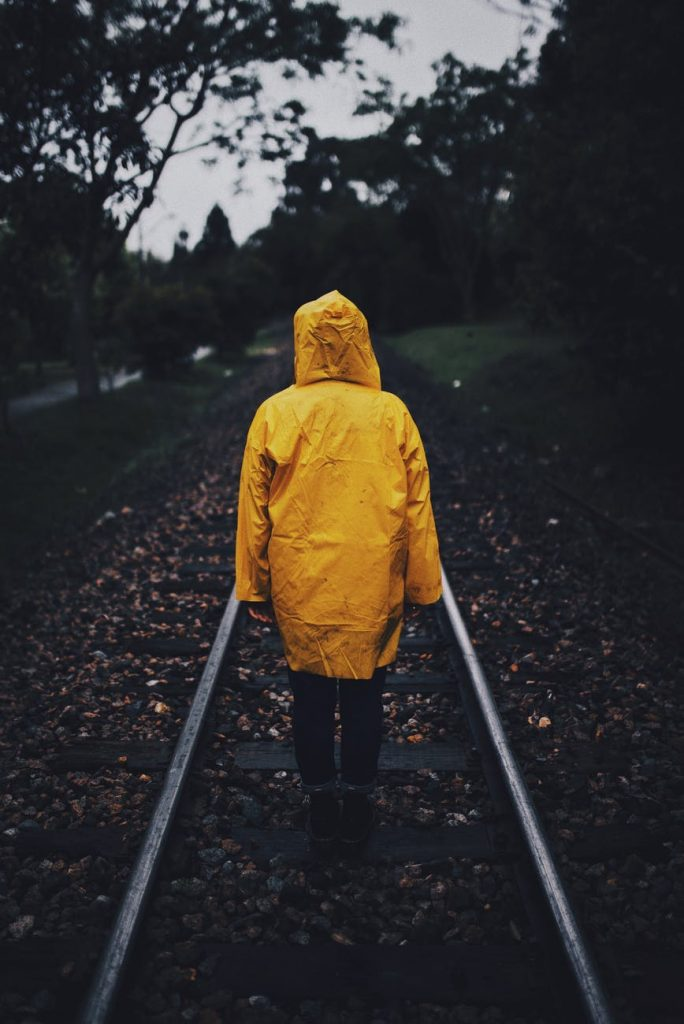 a person walking along the railroad tracks in a rain jacket