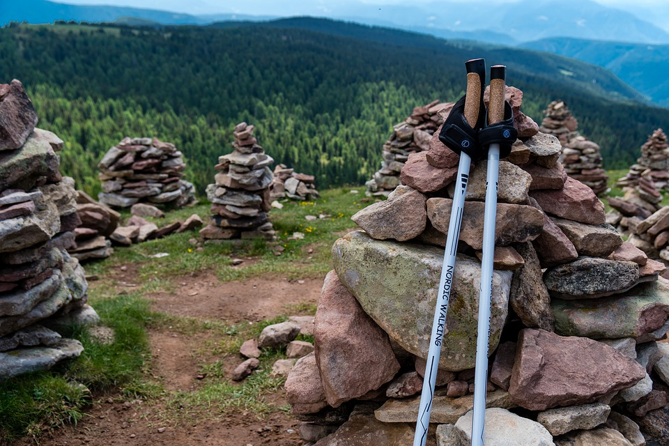 a pair of trekking poles leaned up against a cairn on the side of a trail