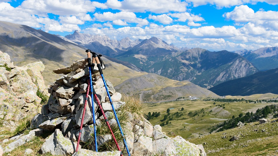trekking poles leaning against a cairn