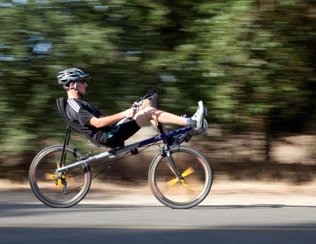 a man riding a short wheelbase recumbent bike