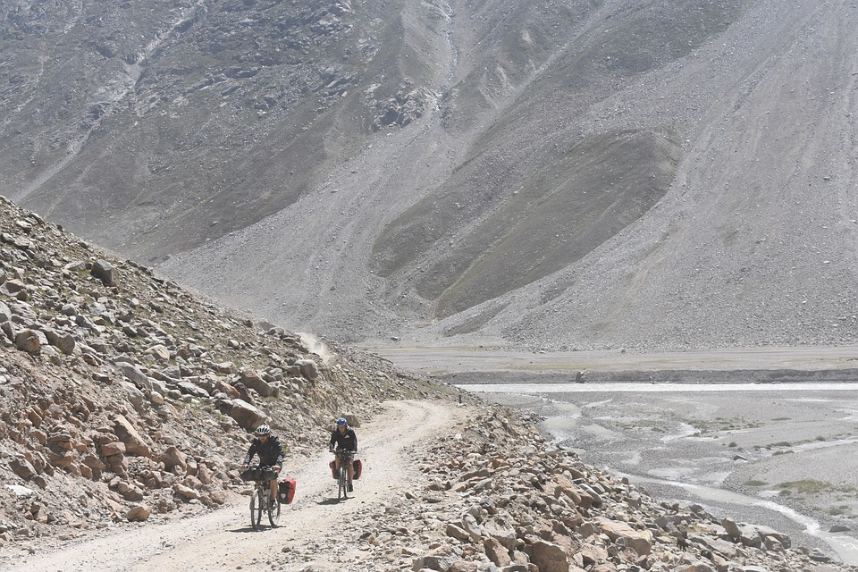 two bicycle tourists riding a dirt road