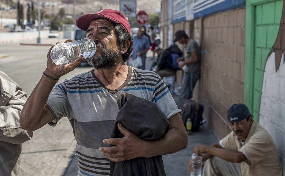a Mexican man drinking bottled water