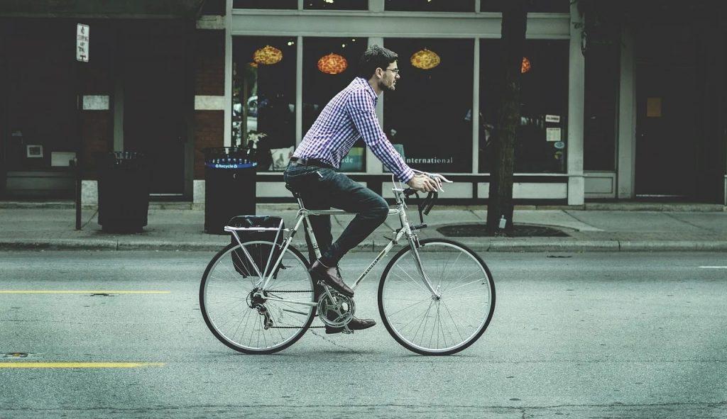 A man riding a geared bike on a city street