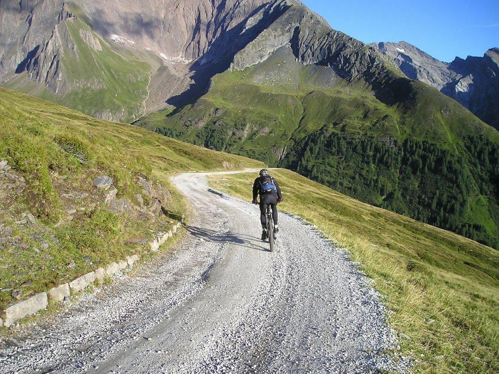 A mountain biker riding don a gravel hill