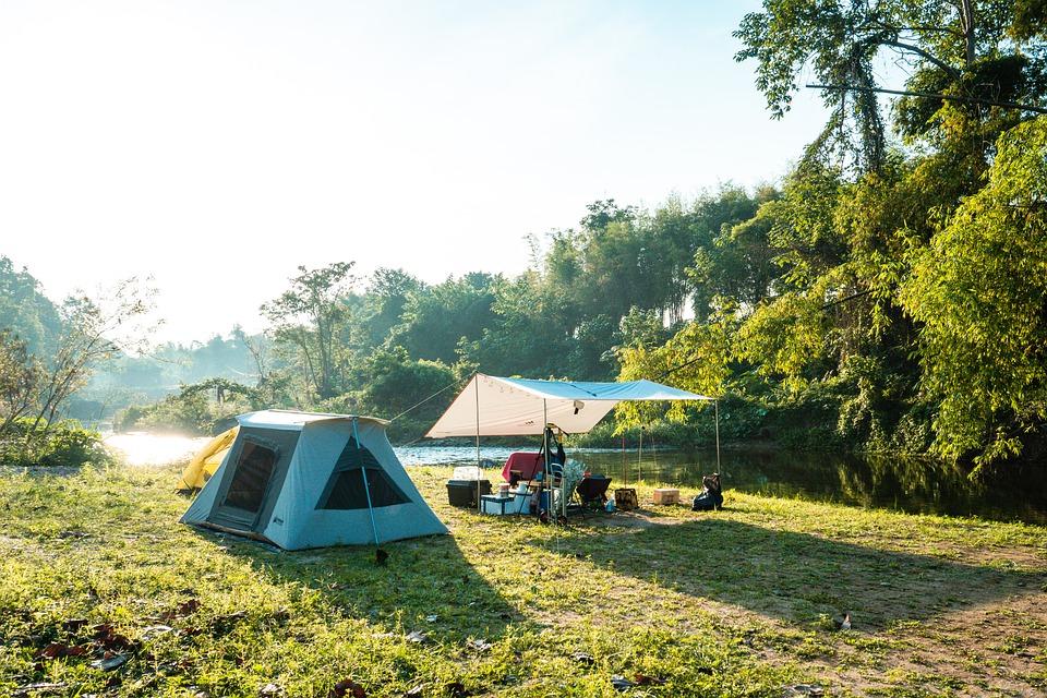 A nice car camping setup with a tent and tarp