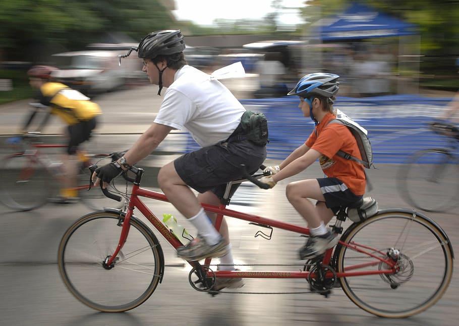 A man and boy riding a tandem bike