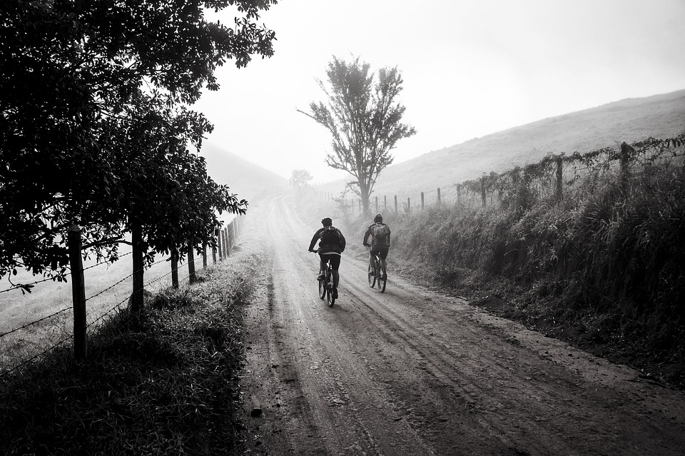 two people riding bikes down a dirt road