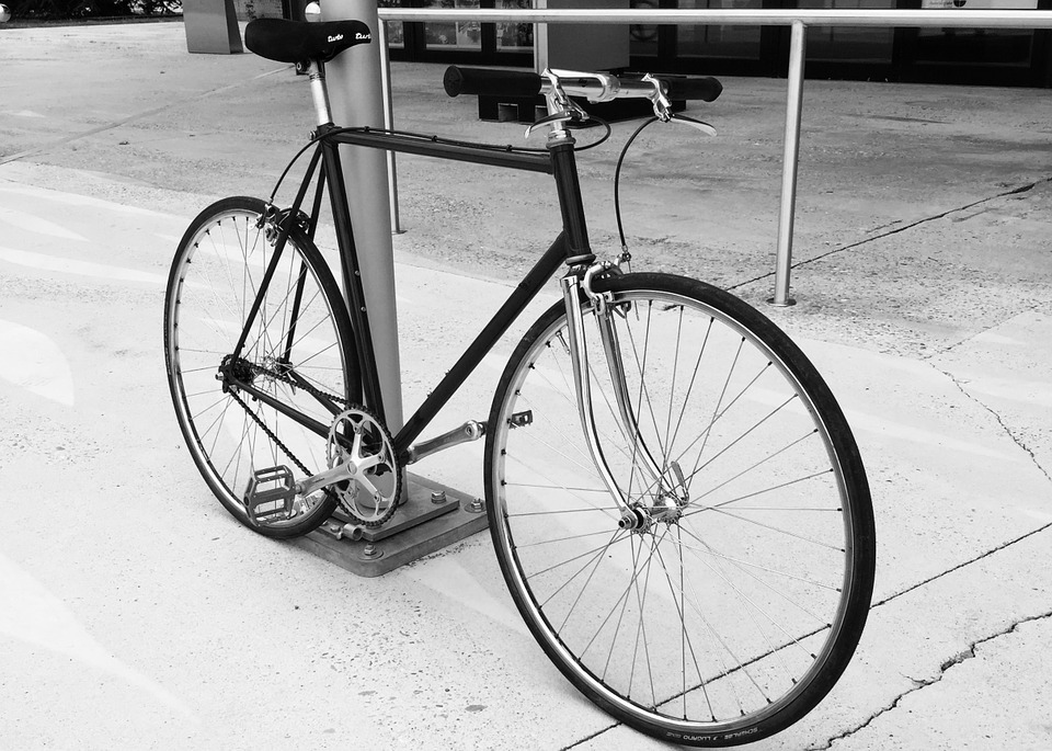 A single speed bike leaning against a pole