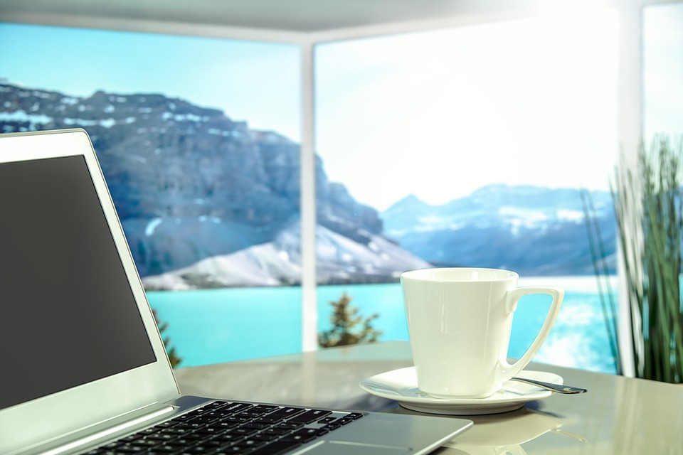 A laptop sitting on a table in front of a mountain view