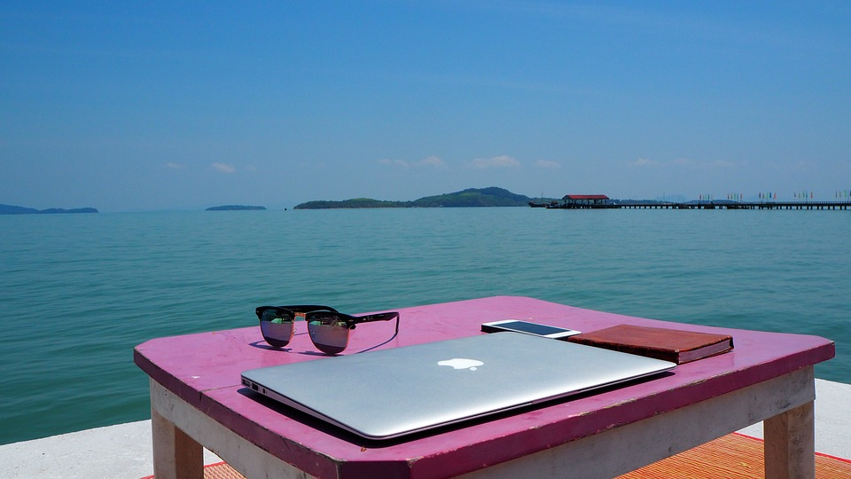 a laptop sitting on a table overlooking the ocean in Thailand